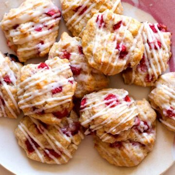 A stack of Strawberry shortcake cookies on a pink plate.