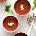 Four bowls of strawberry gazpacho with mint on the side.