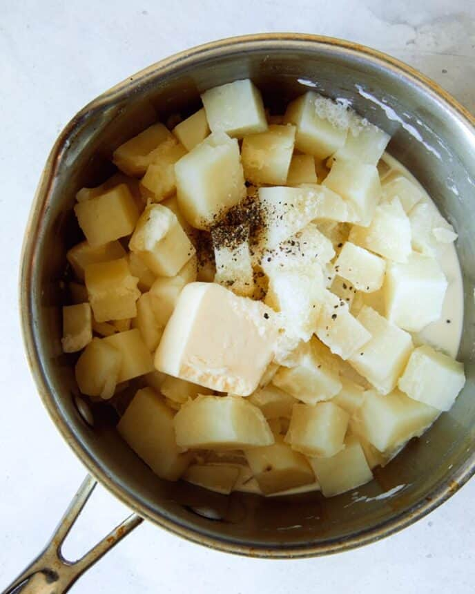 A pot of cooked potatoes with butter and cream, and salt and pepper.