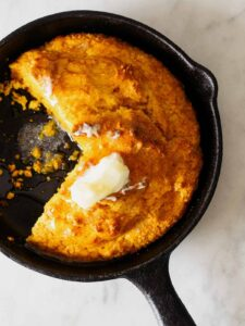 Pumpkin Cornbread in a skillet with butter on top.