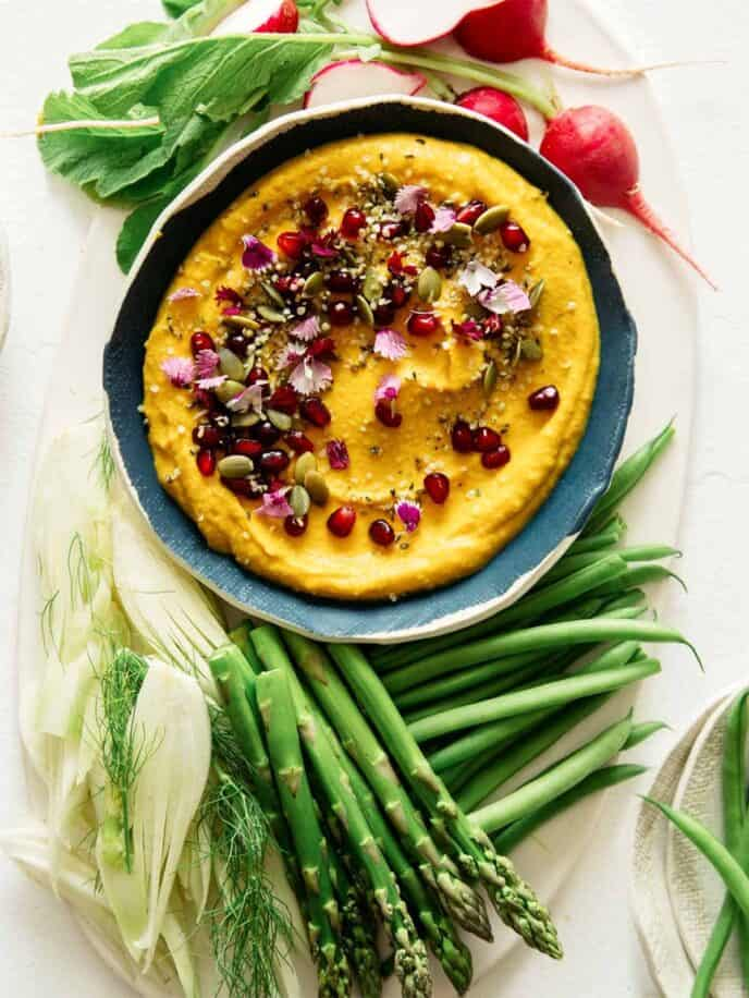 Roasted pumpkin hummus in a bowl with vegetables on the side.