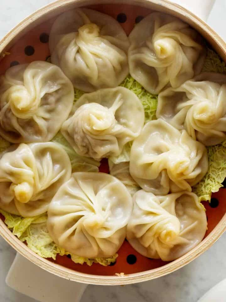 Shanghai Soup Dumplings in a steamer with cabbage.