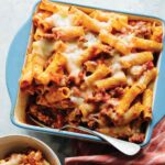 Baked Ziti in a casserole dish with a spoon in it.