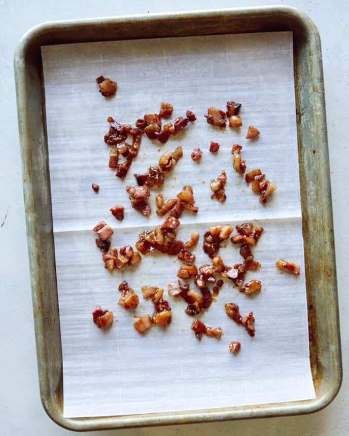 Candied pancetta hardening on a baking sheet.