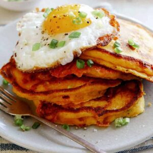 Cheesy Pumpkin Pancakes on a plate with a plate in the background of more pancakes.