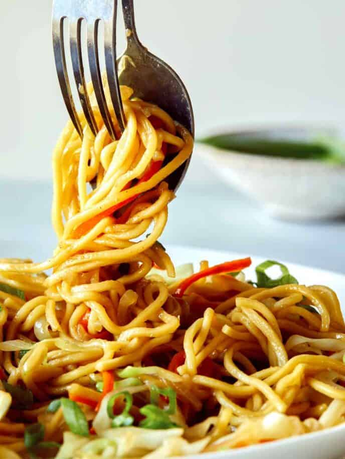 A close up of Chow Mein Noodles being served from a platter.