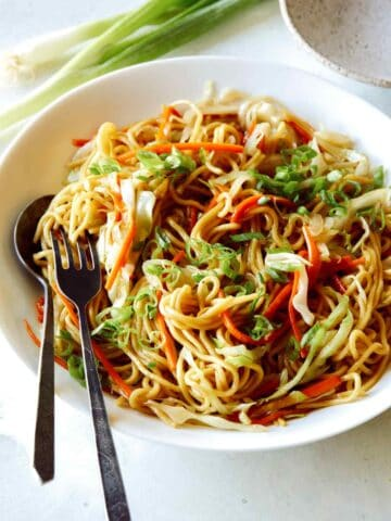 Chow Mein Noodles in a big bowl with a fork and spoon in it to serve.