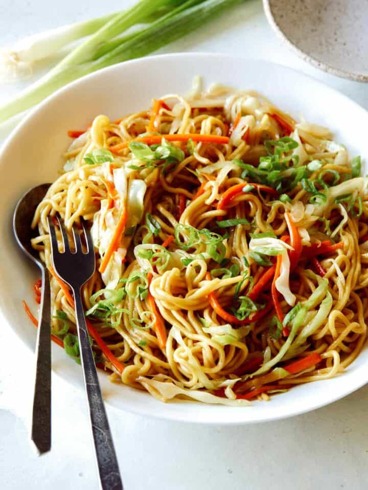 Chow Mein Noodles in a big bowl with a fork and spoon in it to serve, a dinner idea.