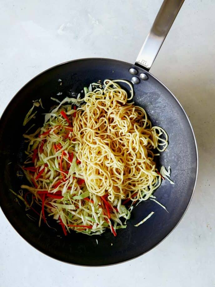 Chow Mein noodles being added to a wok of chow mein vegetables.