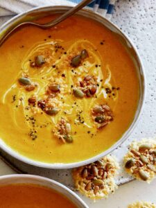 Creamy Pumpkin Soup recipe in a bowl with a spoon in it and parmesan crisps next to it.