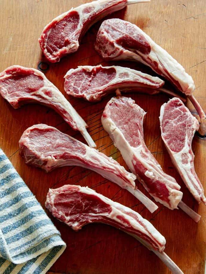 Raw lamb chops on a cutting board.