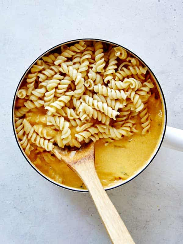 Tossing cooked fusilli pasta into a pot full of pumpkin thyme mac and cheese sauce.