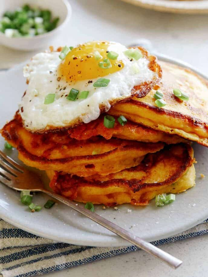 Pumpkin pancakes on a plate with an egg on top.