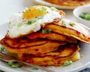 A plate of cheesy pumpkin pancakes with a egg on top of them.