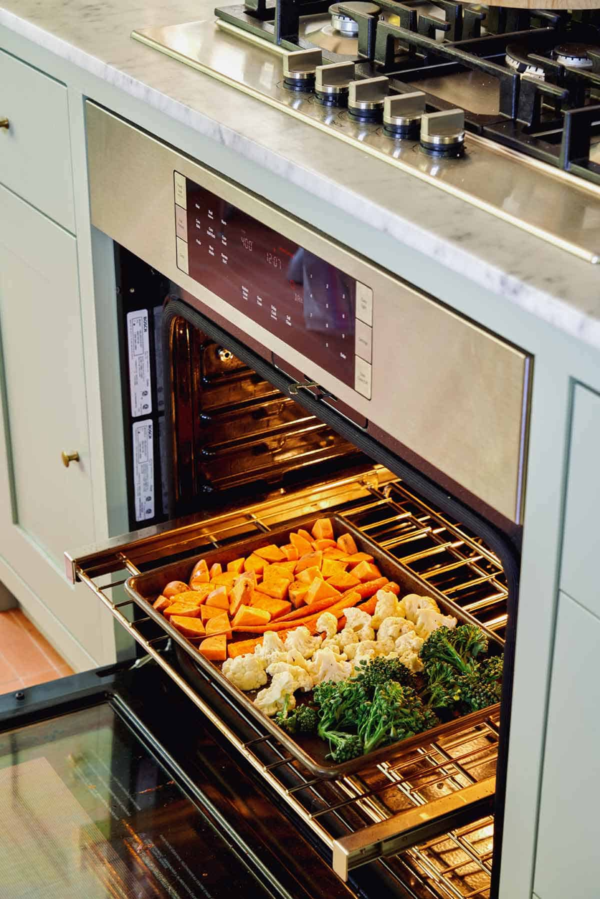 A sheet pan of vegetables going into an oven to roast.