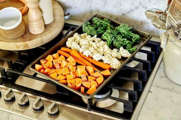 A baking sheet full of cooked vegetables ready to go into an oven.