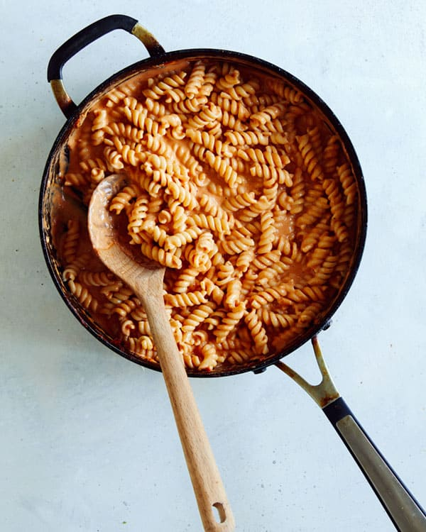 A skillet full of pasta and vodka sauce.