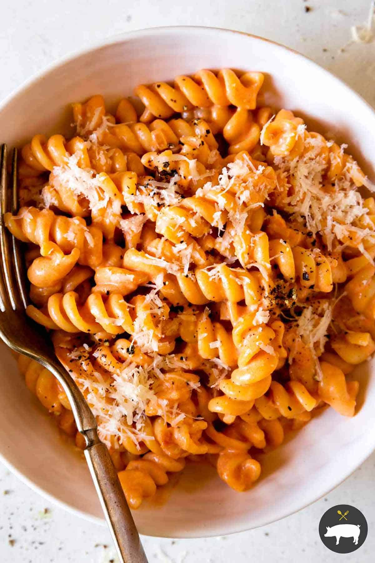heaping bowl of finished rotini tossed in vodka sauce, topped with Parmesan and black pepper with fork off to side and small bowls of crushed red pepper flakes and more grated Parmesan
