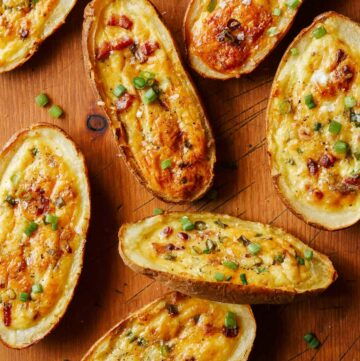 Several potato skin egg boats on wood.