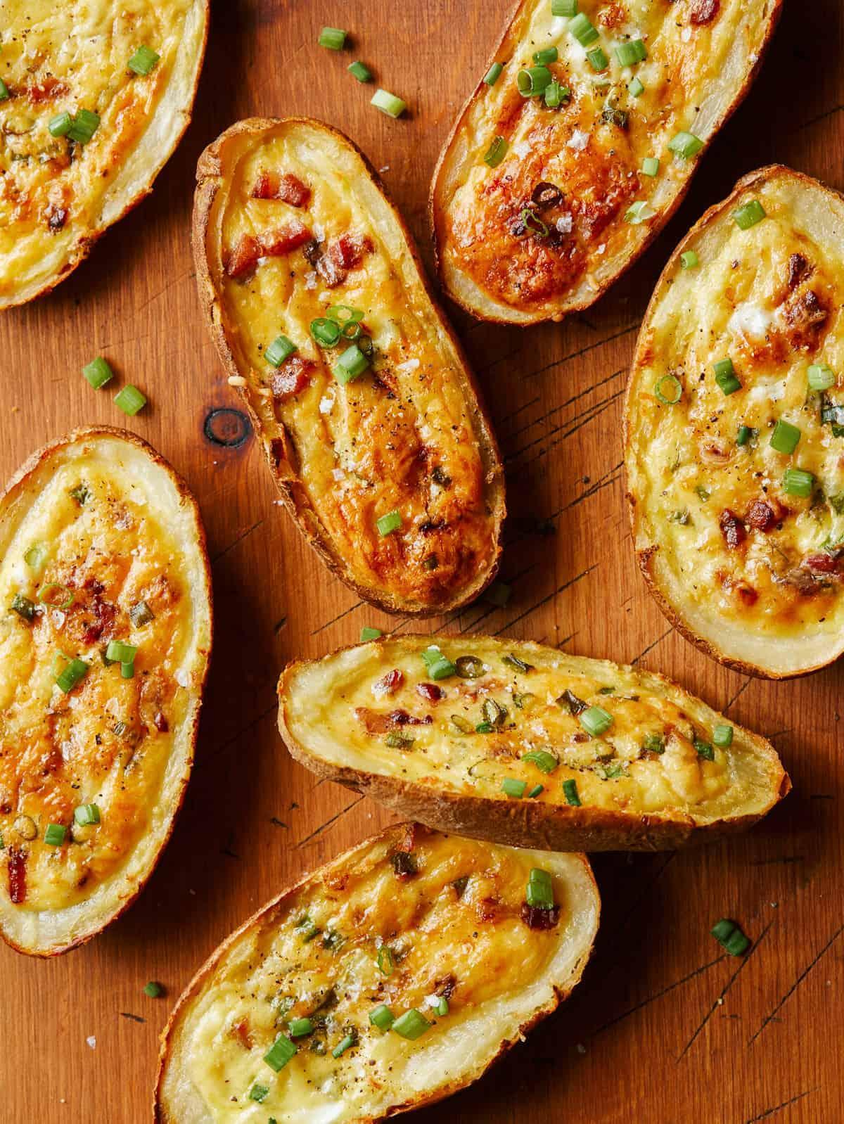 Several potato skin egg boats on wood.