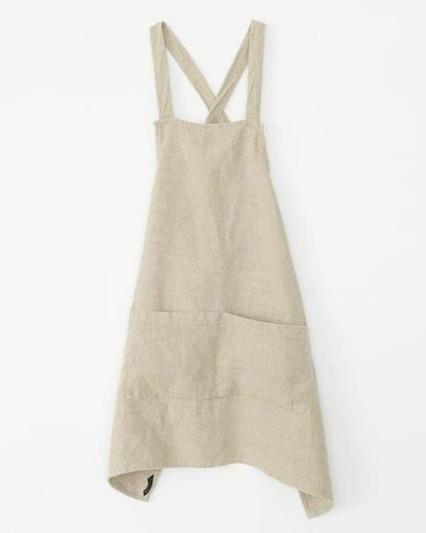 A linen crossback apron on a white background.