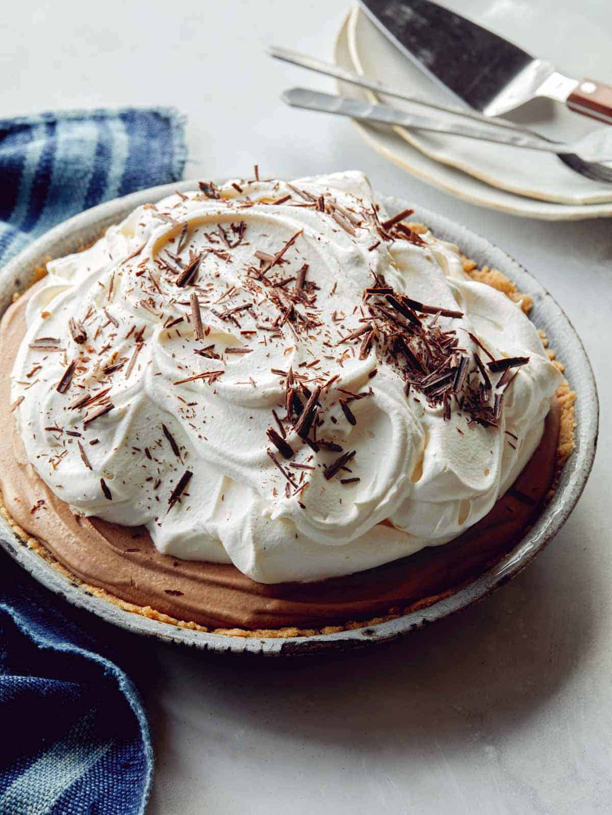 A whole french silk pie with some plates in the background.
