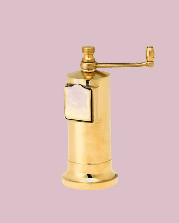A brass pepper mill on a pink background.