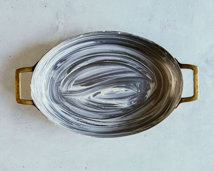 A buttered oval baking dish on a surface.