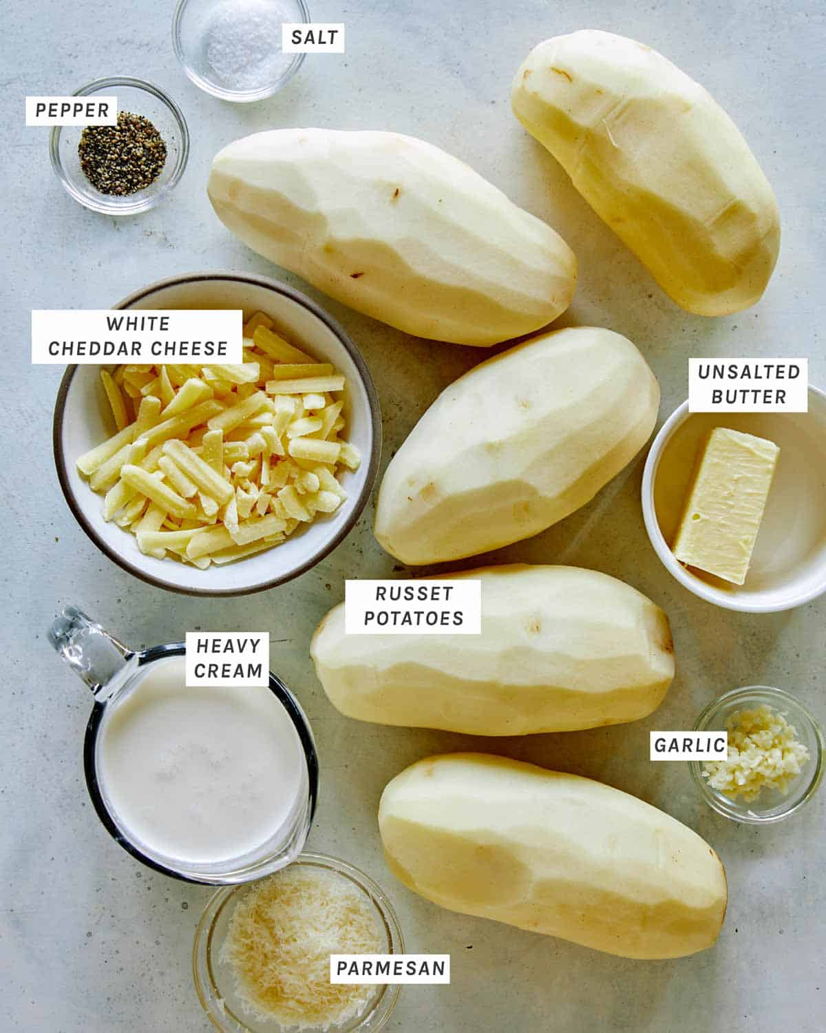 Ingredients for a cheesy potato gratin all laid out on a kitchen counter.