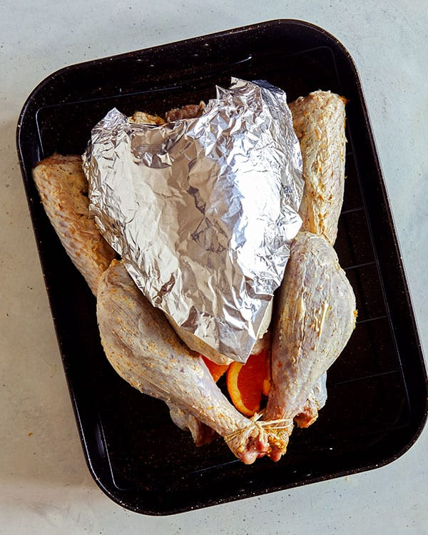 A turkey with a breast covered in tin foil.