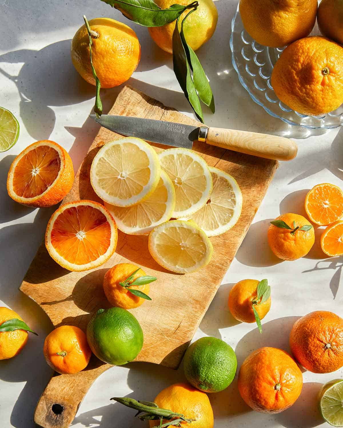 Slicing various kinds of citrus to make dehydrated citrus wheels.