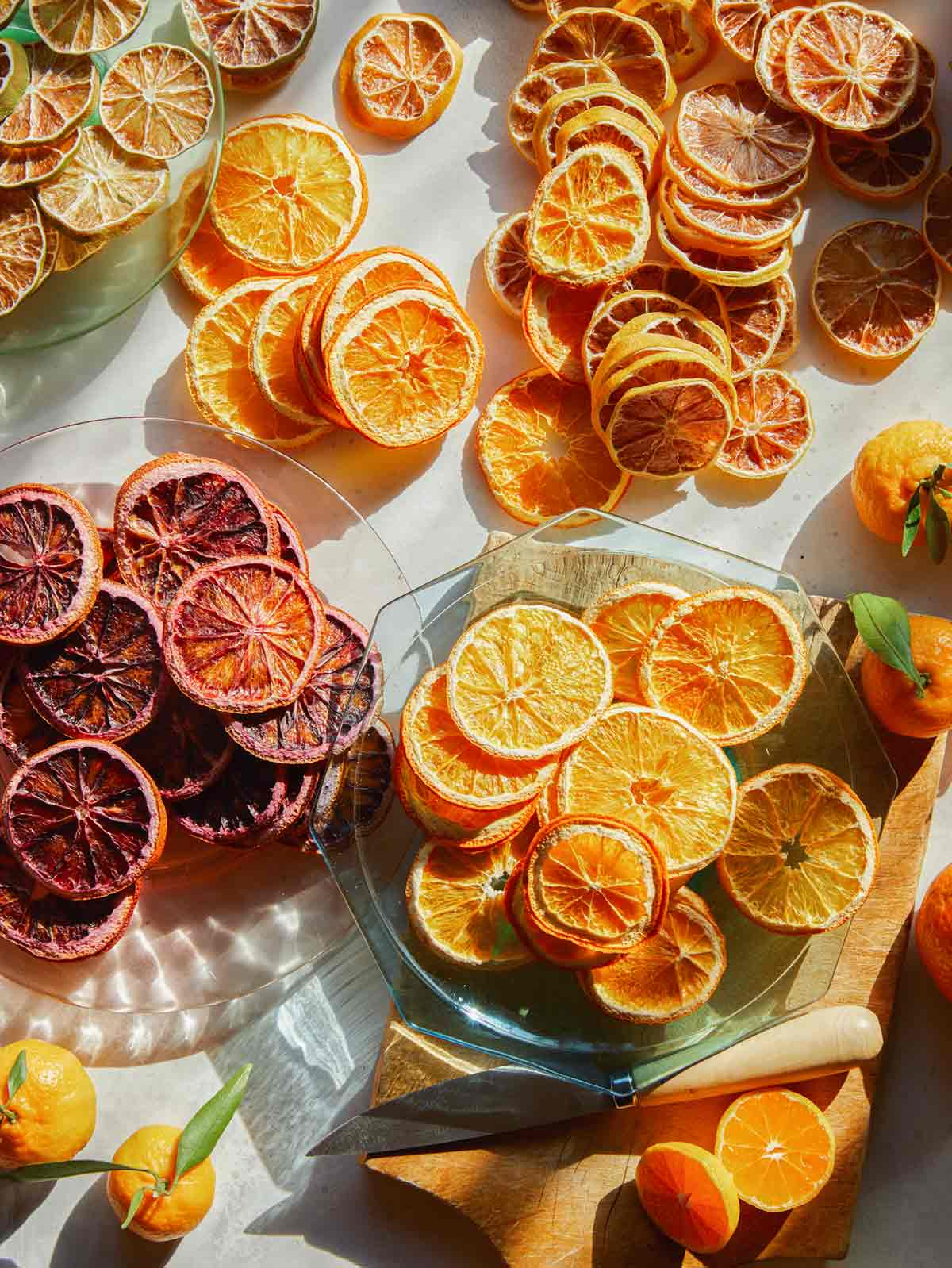 Dehydrated citrus on a surface on plates with fresh citrus.