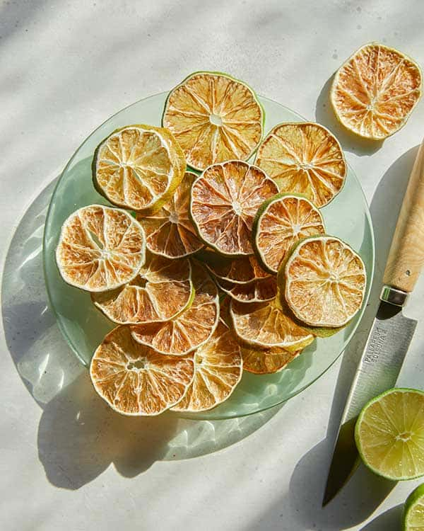Dehydrated lime slices on a plate next to a fresh lime.