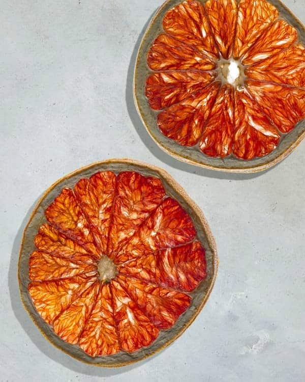 Tranches d'orange sanguine sur une surface blanche.