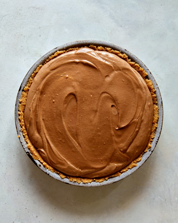 French silk pie in a pie dish waiting for the refrigerator.