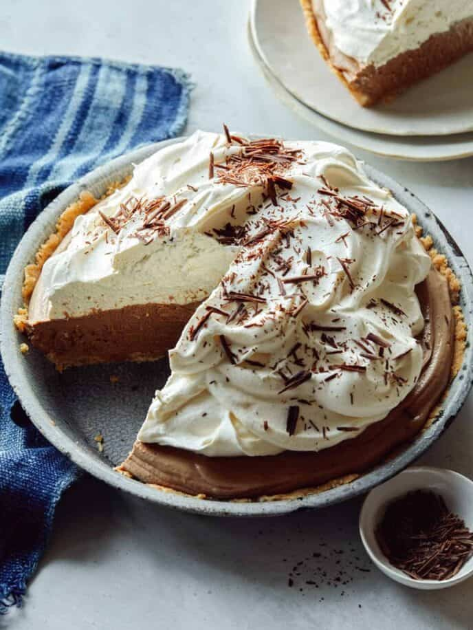 French silk pie with a slice out on a plate next to it.