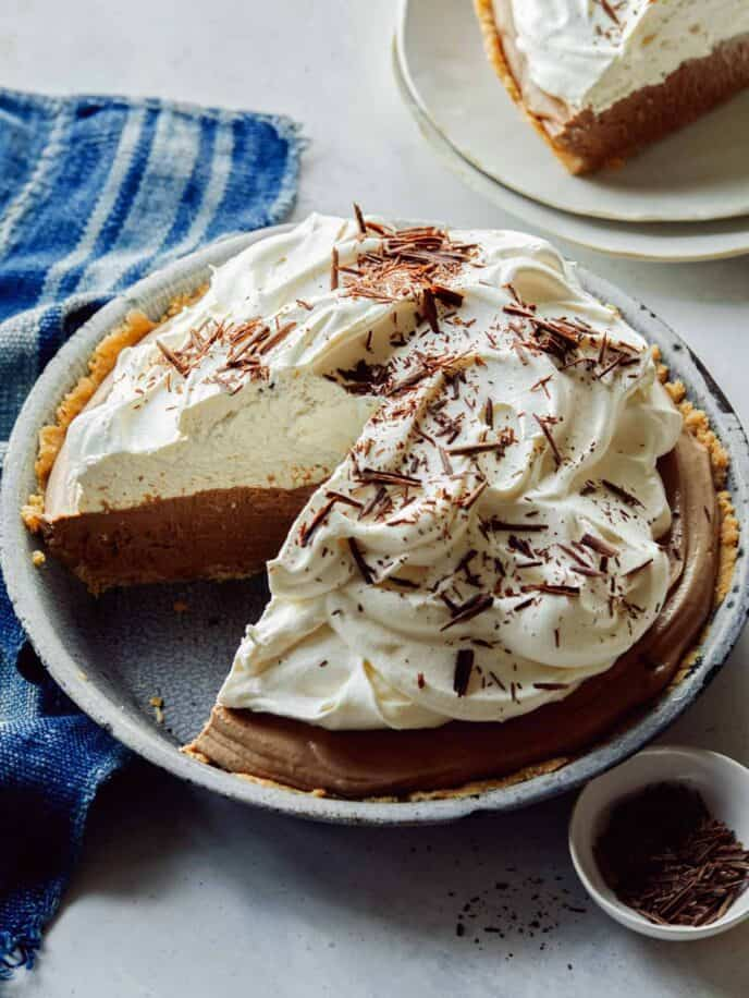 French silk pie in a a pie dish with a slice taken out.