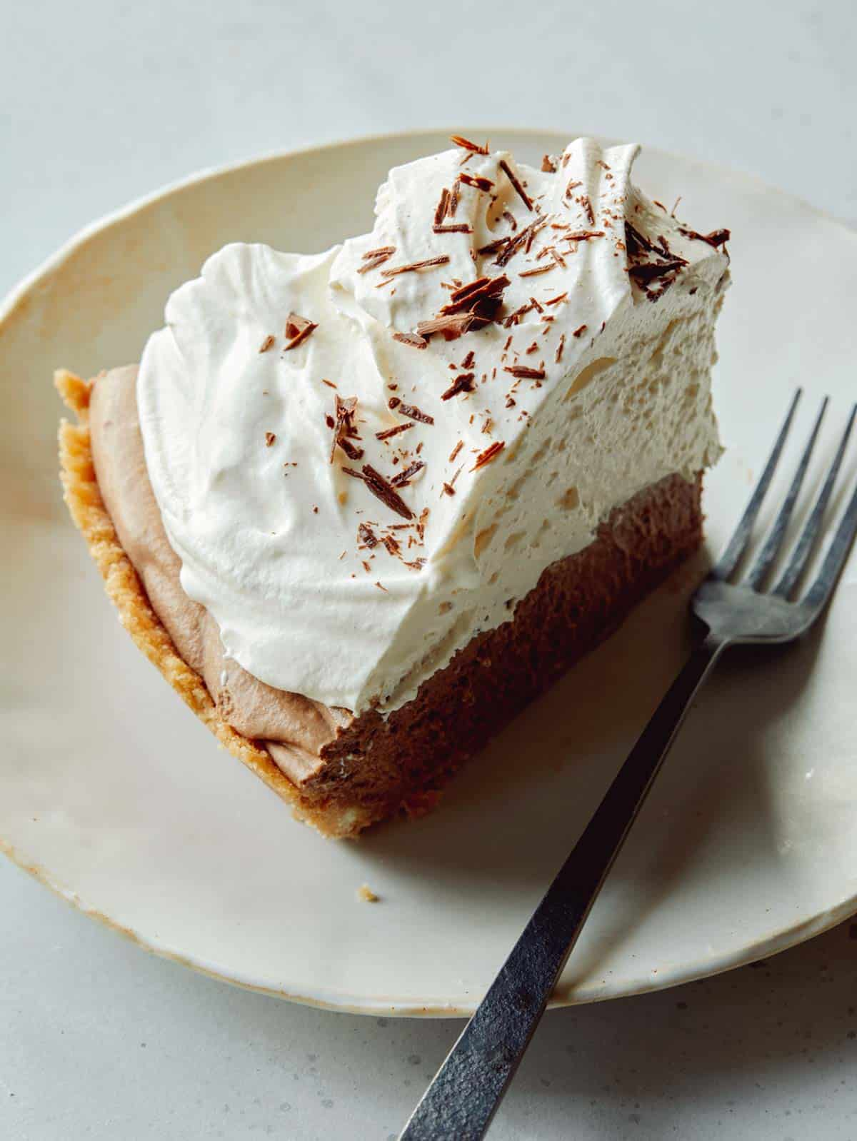 A slice of French silk tart on a plate with a fork next to it.