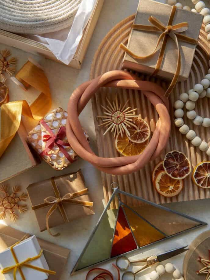 A shot of wrapping gifts with ribbon and Christmas ornaments.