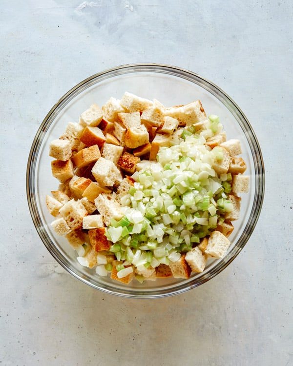 Bread crumbs with celery and onion on top in a glass bowl.