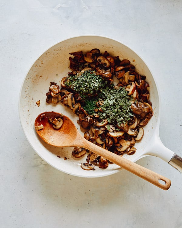 Herbs and mushrooms sauted in a skillet.
