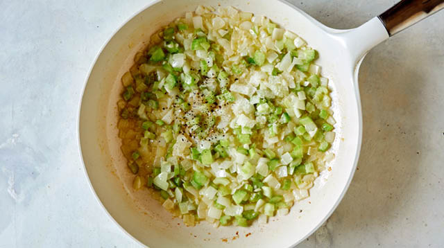 Melt butter and sauté onion, celery and garlic. Season with salt and pepper in a skillet.