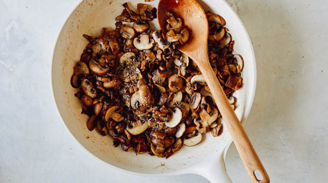 Mushrooms sauted in a skillet.