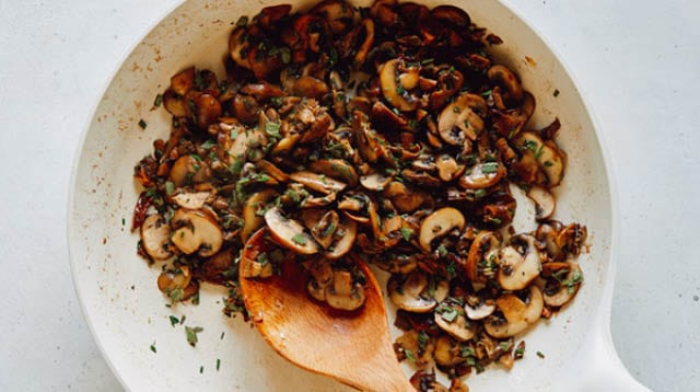 A skillet with mushrooms and herbs.