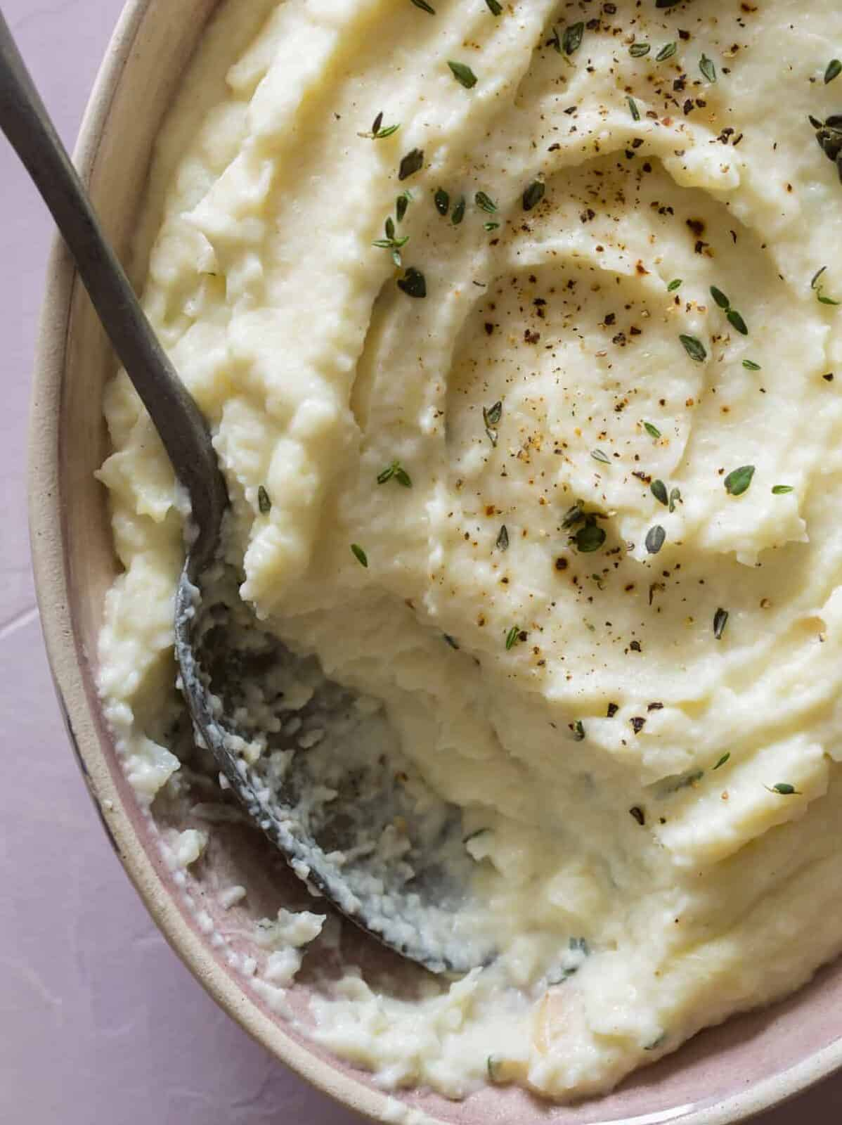 A close up of parsnip, cauliflower, and roasted garlic mash with a spoon.