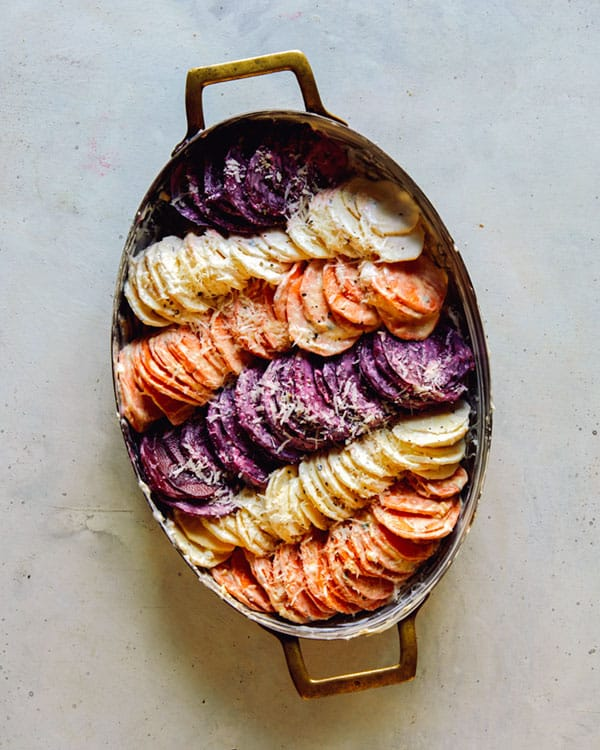 A baking dish full of sliced root vegetables to make a root vegetable gratin.