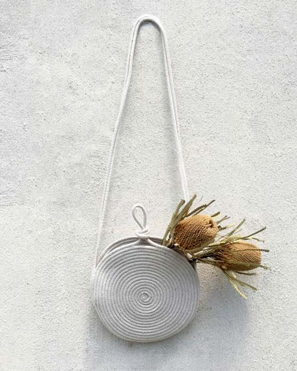 A purse made out of rope with  flowers in it hanging on a wall.
