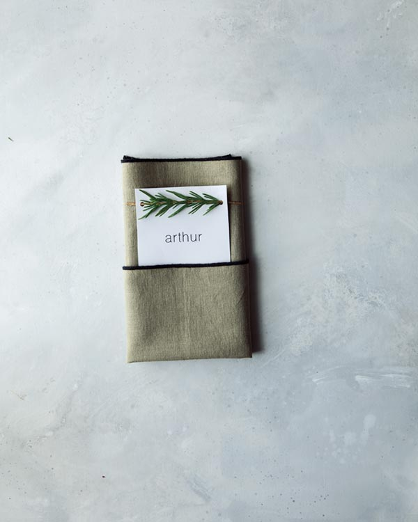 Folding a napkin to create a pocket for rosemary sprig place cards.