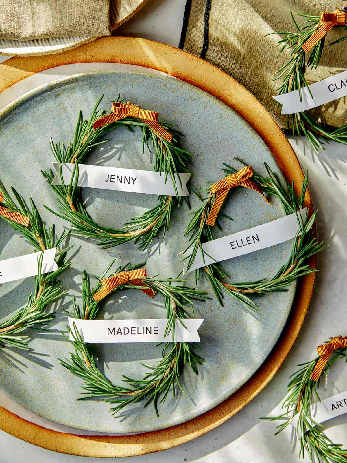 Rosemary wreath place cards with plates and linens.