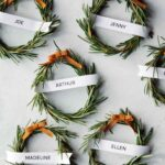 Six rosemary wreath place cards on a table spread out.